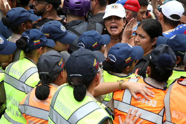 Opposition supporters argue with riot police during a rally against Venezuelan President Nicolas Maduro's government and to commemorate the 59th anniversary of the end of the dictatorship of Marcos Perez Jimenez in Caracas, Venezuela January 23, 2017. (Photo by Carlos Garcia Rawlins/Reuters)