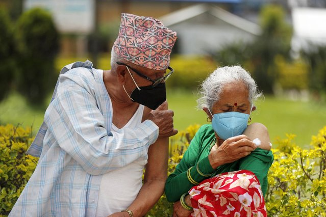 An elderly Nepalese couple hold their arms after receiving AstraZeneca COVID-19 vaccine in Kathmandu, Nepal, Monday, August 9, 2021. (Photo by Niranjan Shrestha/AP Photo)