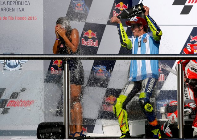 Yamaha MotoGP rider Valentino Rossi of Italy sprays champagne at a grid girl on the podium after winning Argentina's MotoGP Grand Prix at the Termas de Rio Hondo International circuit in Termas de Rio Hondo, April 19, 2015. (Photo by Marcos Brindicci/Reuters)