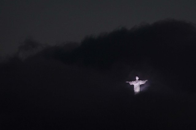 The Christ the Redeemer statue, surrounded by clouds, is lit up at dusk on June 7, 2013. (Photo by Felipe Dana/Associated Press)