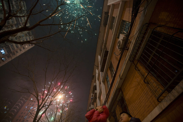 A Chinese girl covers her ears as residents set off fireworks on the eve of Lunar New Year in Beijing, China, Friday, January 27, 2017. Chinese worldwide celebrate the Year of the Rooster on Jan 28, 2017 with family reunions and fireworks. (Photo by Ng Han Guan/AP Photo)