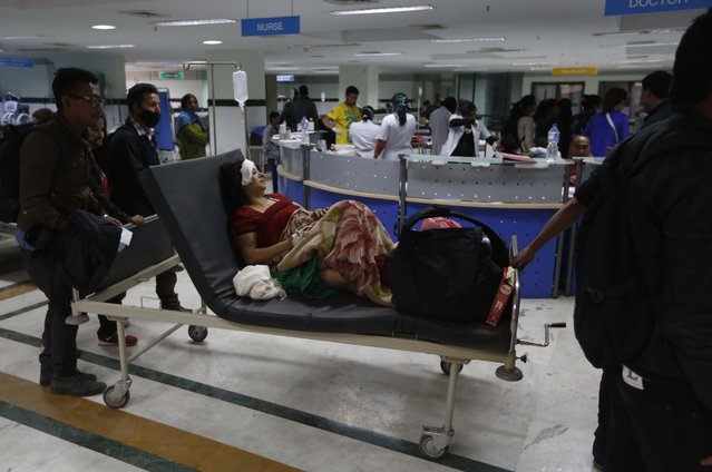 An earthquake injured woman lies on a mobile bed at a hospital in Kathmandu, Nepal, Sunday, April 26, 2015. (Photo by Manish Swarup/AP Photo)