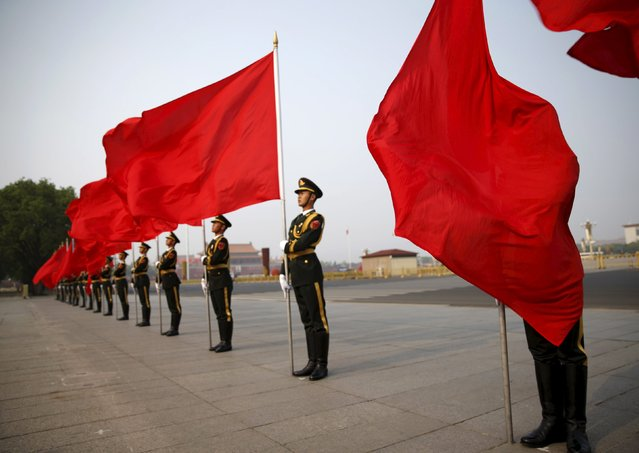 The wind blows a red flag onto the face of an honour guard before a welcoming ceremony for Algeria's Prime Minister Abdelmalek Sellal outside the Great Hall of the People in Beijing, China, April 29, 2015. (Photo by Kim Kyung-Hoon/Reuters)