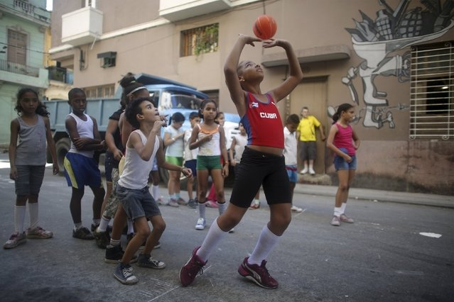 Amanda Bonnell (C), 8, exercises with schoolmates on a street in downtown Havana, February 24, 2016. (Photo by Alexandre Meneghini/Reuters)