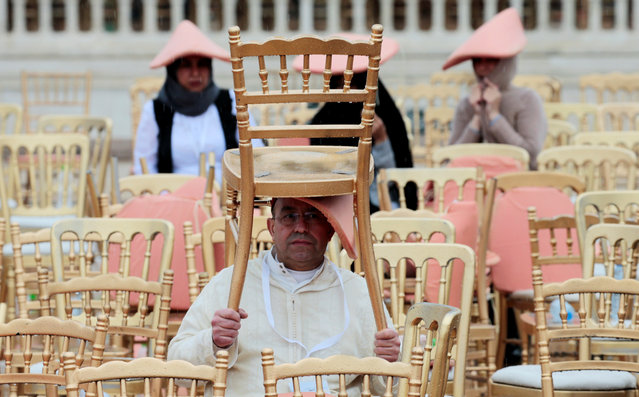 A man uses a chair to cover himself from the rain as he waits for the arrival of Pope Francis at the Hassan Tower esplanade in Rabat, Morocco, March 30, 2019. (Photo by Youssef Boudlal/Reuters)