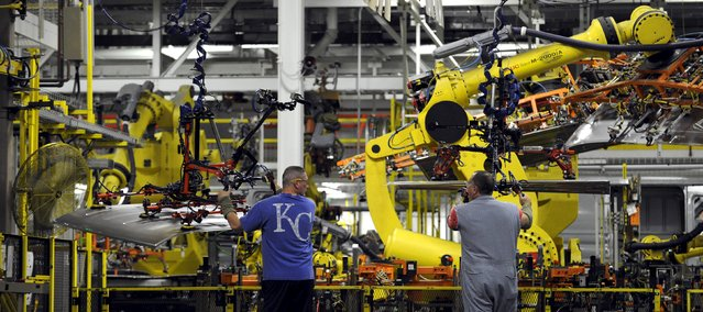 Auto workers feed aluminum panels to robots at Ford's Kansas City Assembly Plant where new aluminum intensive Ford F-Series pickups are built in Claycomo, Missouri May 5, 2015. (Photo by Dave Kaup/Reuters)