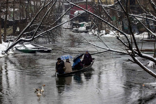 A Kashmiri family travels in a boat as it rains in the interiors of the Dal Lake on the outskirts of Srinagar, Indian controlled Kashmir, Sunday, February 5, 2017. Authorities have issued avalanche warnings for many parts of the region, as the heavy snowfall has cut off roads, disrupted power and communication lines. (Photo by Dar Yasin/AP Photo)