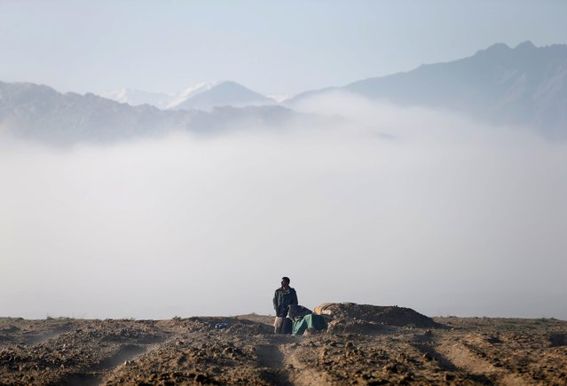 "An Afghan hunter watches birds in the sky at a hunting field in Bagram, Parwan province, Afghanistan on April 10, 2019. ""The pleasure of hunting is to be in open space. I like the mountain, desert, shotgun and being awake during the night to hunt"", he said. ""The pleasure of hunting is to be a success in it. A hunter's hope is hunting. Being a success in every job in the world has a special pleasure"". (Photo by Mohammad Ismail/Reuters)"