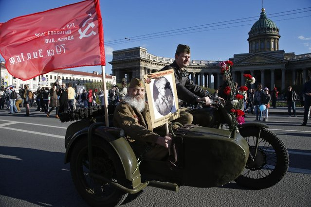 Valery Kutsalov wearing a Soviet army uniform holds a portrait  of his father, a participant in World War Two during celebration of the 70th anniversary of the defeat of the Nazis in World War II in St. Petersburg, Russia, Saturday, May 9, 2015. (Photo by Dmitry Lovetsky/AP Photo)