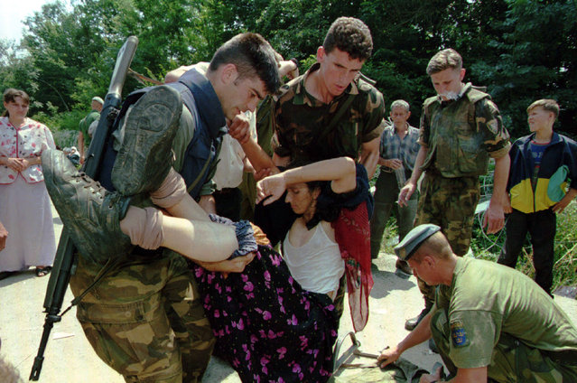 Bosnian government soldiers help a refugee from Srebrenica who collapsed from exhaustion upon arrival at the UN compound at Tuzla airport, July 1995. (Photo by Reuters)