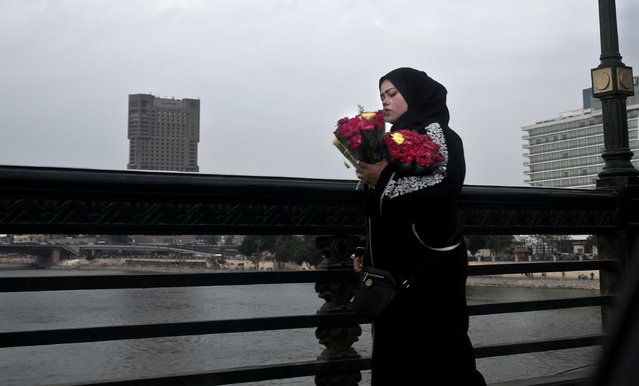 A woman tries to sell roses on Valentine's Day in Cairo, Egypt, Tuesday, February 14, 2017. (Photo by Nariman El-Mofty/AP Photo)