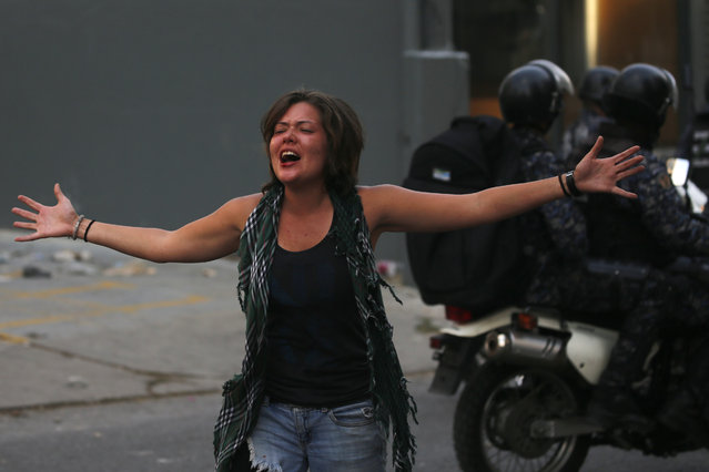 A woman cries out as National Police drive away with detained anti-government protesters on a motorcycles, during clashes between protesters and security forces, in Caracas, Venezuela, Wednesday, May 1, 2019. (Photo by Fernando Llano/AP Photo)