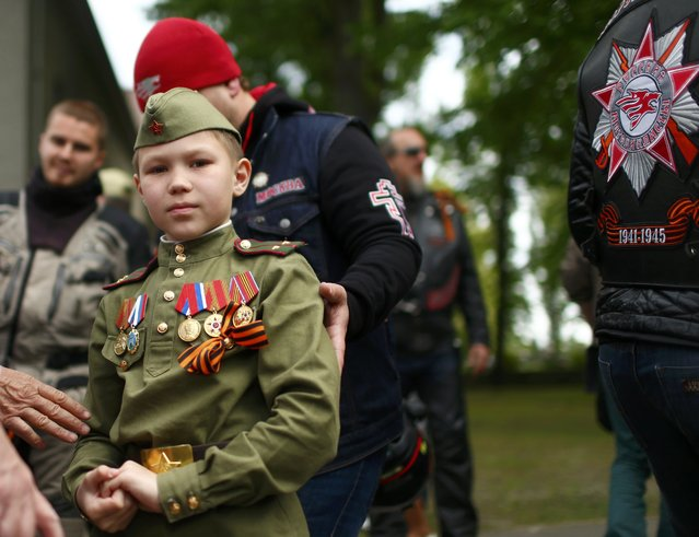 A boy dressed in a replica of the Red Army soldier uniform stands with the members of the Russian motorcycle group called Night Wolves ride near the German-Russian museum Berlin-Karlshorst in Berlin, Germany, May 8, 2015. Members of the Night Wolves, a motorcycle group blacklisted by the United States for taking part in Russia's annexation of Crimea, and supporters are taking part in a bike ride from Moscow to Berlin, commemorating the end of World War Two. (Photo by Hannibal Hanschke/Reuters)