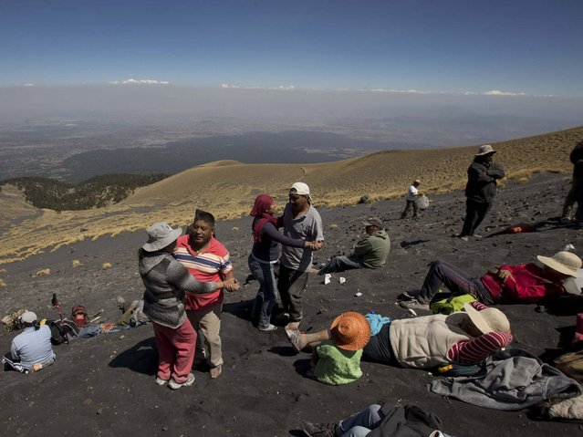 People who live in nearby villages dance on the slope of the of the Popocatepetl volcano in Mexico. (Photo by Eduardo Verdugo/AP Photo)