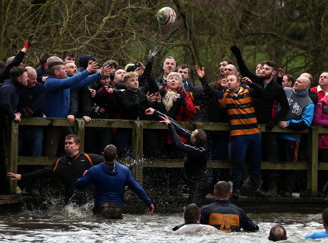 The ball breaks from the hug during the annual Shrovetide football match in Ashbourne, Derbyshire, Britain, 28 February 2017. The game which dates back to the 17th century is played by two teams, the Up'ards and the Down'ards. The aim of the game is to score by tapping the ball three times on stone goal plinths which are three miles apart on the banks of the River Henmore. (Photo by Nigel Roddis/EPA)