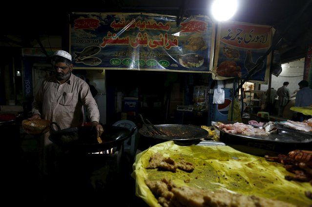 A man prepares fish under lights powered by a generator at his stall in Islamabad April 9, 2015. (Photo by Caren Firouz/Reuters)