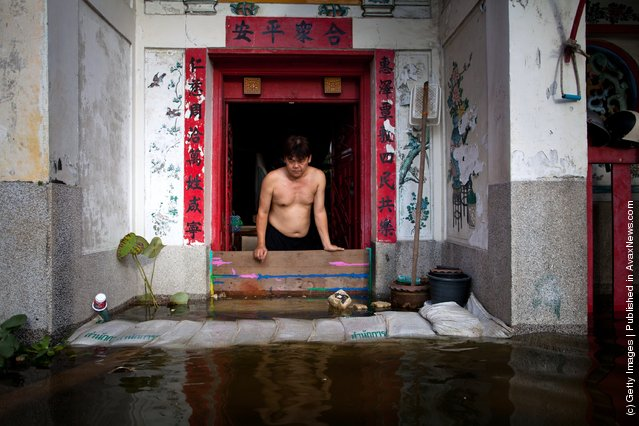 A man looks down at rising flood waters encroaching on a Chinese temple in China Town near to the overflowing Chao Phraya river