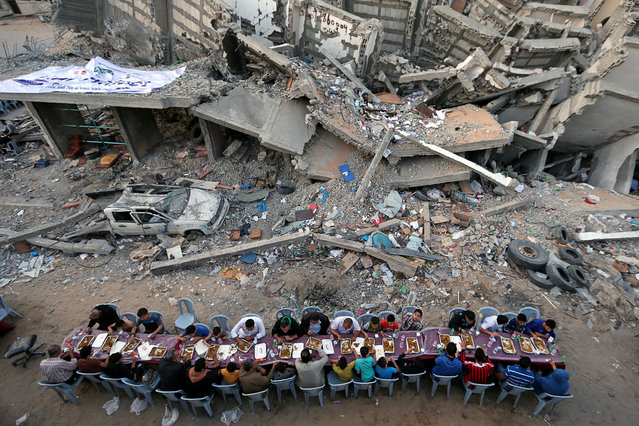 Palestinians break their fast by eating the Iftar meals during the holy month of Ramadan, near the rubble of a building recently destroyed by Israeli air strikes, in Gaza City on May 18, 2019. (Photo by Ibraheem Abu Mustafa/Reuters)