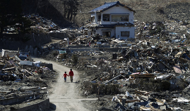 People walk at an area that was damaged by the March 11 earthquake and tsunami, in Miyako, Iwate prefecture, April 5, 2011. (Photo by Toru Hanai/Reuters)