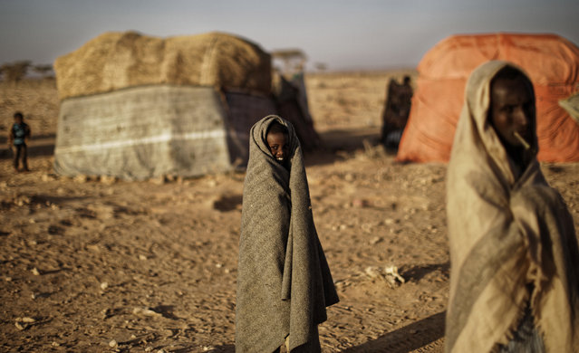 In this photo taken Thursday, March 9, 2017, a boy who fled the drought covers himself with a blanket in front of makeshift huts in a camp for the displaced in Qardho in Somalia's semiautonomous northeastern state of Puntland. (Photo by Ben Curtis/AP Photo)