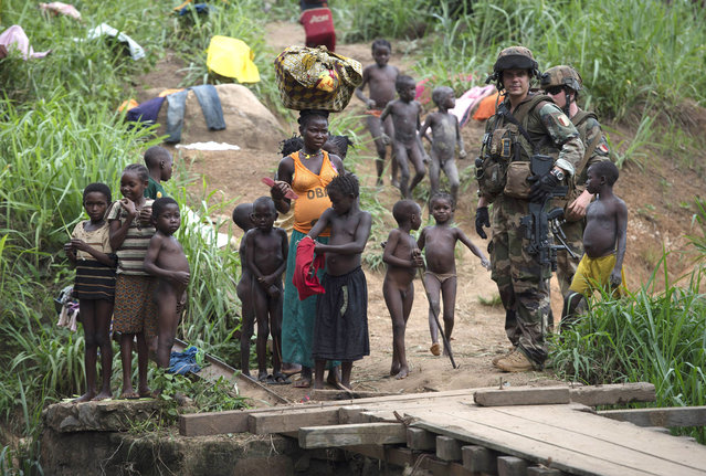 French soldiers of the 13th Alpine Hunters Battalion (13th BCA) stand beside children as they patrol near the northwestern city of Boda on April 7, 2014. Thousands of people have been killed in a wave of sectarian violence across the Central African Republic that has lasted for more than a year, despite the presence of African Union and French peacekeeping troops. (Photo by Miguel Medina/AFP Photo)
