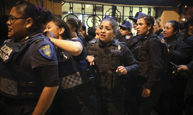Police watch the second floor of their station burn, set on fire by protesters during a demonstration sparked by a string of alleged sexual attacks by police officers, in Mexico City, Friday, August 16, 2019. On Friday, hundreds of women demonstrated largely peacefully in downtown Mexico City. But some protesters trashed the nearby bus station and a police station. This week, an auxiliary policeman was held for trial on charges he raped a young female employee at a city museum. (Photo by Emilio Espejel/AP Photo)