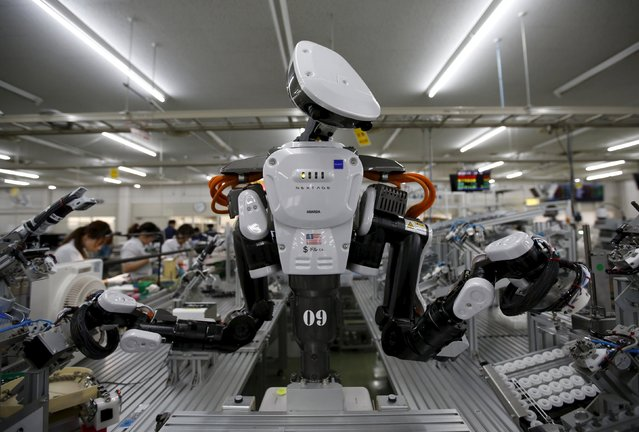 A humanoid robot works side by side with employees in the assembly line at a factory of Glory Ltd., a manufacturer of automatic change dispensers, in Kazo, north of Tokyo, Japan, July 1, 2015. Japanese firms are ramping up spending on robotics and automation, responding at last to premier Shinzo Abe's efforts to stimulate the economy and end two decades of stagnation and deflation. (Photo by Issei Kato/Reuters)