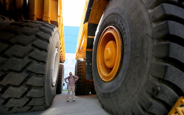 A visitor is dwared between the wheels of BelAZ 450-ton dump truck (L) and BelAZ 360-ton dump truck (R) at the plant of Belarusian manufacturer of heavy trucks and equipment for earthmoving, BelAZ, in Zhodino, some 55 km from Minsk, Belarus, 27 August 2019. The company mostly delivers its products to CIS mining companies, mainly from Russia and Ukraine. (Photo by Tatyana Zenkovich/EPA/EFE/Rex Features/Shutterstock)