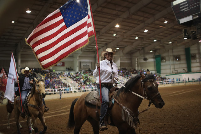 Carolyn Carter carries the American flag as contestants parade through the arena before the start of competition at the Bill Pickett Invitational Rodeo on March 31, 2017 in Memphis, Tennessee. (Photo by Scott Olson/Getty Images)