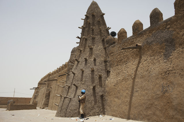 Timbuktu: A UN peacekeeper from Burkina Faso stands guard at the Djinguereber mosque, built in the 14th century, during a visit by a UN delegation on election day in Timbuktu, Mali, July 28, 2013. (Photo by Joe Penney/Reuters)