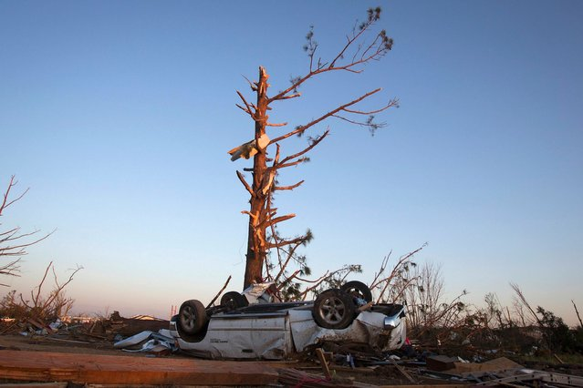 An upturned truck lies under a tree that has lost most of its branches, following a tornado near Vilonia, Arkansas, at sunset April 28, 2014. On a second day of ferocious storms that have claimed at least 19 lives in the southern United States, a tornado tore through the Mississippi town of Tupelo on Monday causing widespread destruction to homes and businesses, according to witnesses and local emergency officials. (Photo by Carlo Allegri/Reuters)