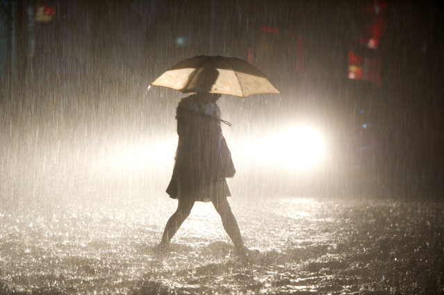 A woman walks on a flooded street during heavy rainfall in Beijing on July 21, 2012. Over 60 percent of Beijing's annual rainfall falls in July and August when as the East Asian monsoon brings relief from the city's usually dry and arid climate. (Photo by Ed Jones/AFP Photo)