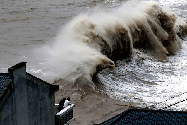 Two people watch huge waves from a balcony as typhoon Chan-hom comes near Wenling, east China's Zhejiang province on July 10, 2015. (Photo by AFP Photo)