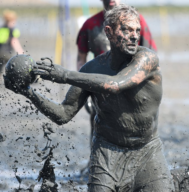 """A player throws a ball during a handball match at the so called """"Wattoluempiade"""" (Mud Olympics) in Brunsbuettel at the North Sea, July 11, 2015. (Photo by Fabian Bimmer/Reuters)"""