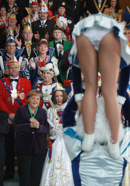 German Chancellor Angela Merkel watches two Carnival dancers perform at a reception of German Carnival delegates and performers at the Chancellery