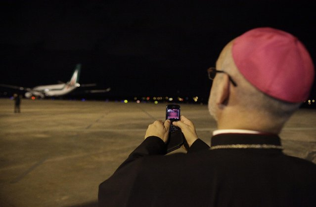 A Prelate captures a photo of Pope Francis' jetliner as is taxi's off into the runway, in Asuncion, Paraguay, Sunday, July 12, 2015. In a week long tour to some of South America's poorest countries the Pope started his trip back to Rome after visiting Ecuador, Bolivia and Paraguay. (Photo by Cesar Olmedo/AP Photo)