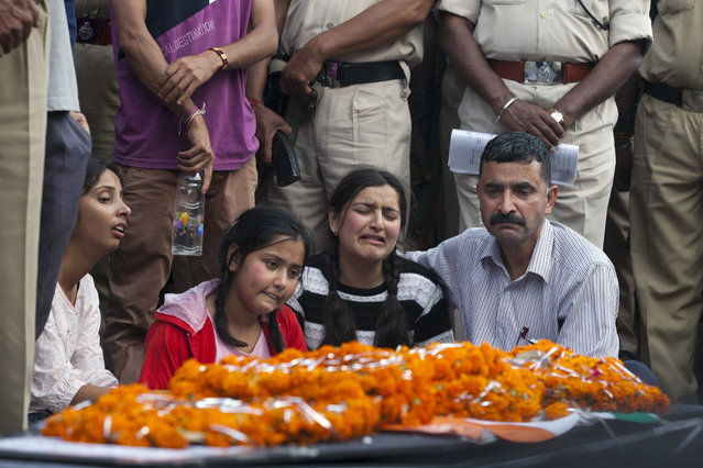Daughters Amisha, second right and Kashish, second left, mourn next to the coffin of Indian paramilitary soldier Sanjay Kumar at a crematorium in Palampur, about 40 kilometers (25 miles) south of Dharmsala, India, Tuesday, April 25, 2017. Kumar was among 25 Indian paramilitary soldiers who were killed by Maoist rebels in central India on Monday in one of the worst attacks on the country's security forces in recent years. (Photo y Ashwini Bhatia/AP Photo)