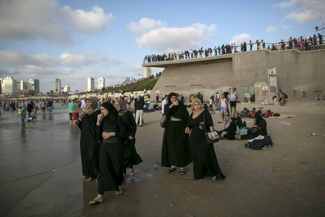 Muslims, most from the West Bank and East Jerusalem, walk on a beach of the Mediterranean in Tel Aviv during Eid al-Fitr, which marks the end of the holy month of Ramadan, July 19, 2015. (Photo by Baz Ratner/Reuters)