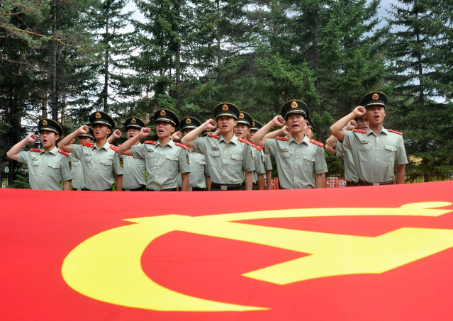 Chinese paramilitary policemen pledge loyalty to the Communist Party as they observe the 94th anniversary of the founding of the Communist Party of China in Mohe county in northeastern China's Heilongjiang province Wednesday, July 1, 2015. (Photo by Chinatopix Via AP Photo)