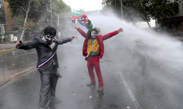 "Men dressed as clowns, one dressed as the the movie character ""The Joker"" flying a Mapuche indigenous flag, are sprayed by a police water cannon during an anti-government protest in Santiago, Chile, Monday, November 4, 2019. Chile has been facing weeks of unrest, triggered by a relatively minor increase in subway fares. The protests have shaken a nation noted for economic stability over the past decades, which has seen steadily declining poverty despite persistent high rates of inequality. (Photo by Esteban Felix/AP Photo)"