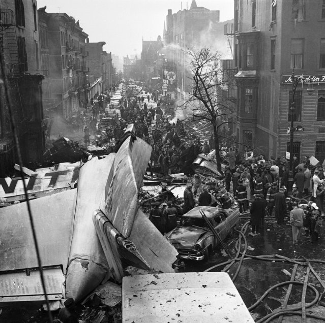 Tail section of UAL airliner blocks intersection of two streets in heavily populated area of Brooklyn, December 16, 1960 after plane crashed as it approached Idlewild Airport for a landing. A section of planes wing can be seen at base of tree at right center. In background is block of apartment set ablaze when plane crash. Intersection at 7th avenue and sterling place. (Photo by AP Photo)