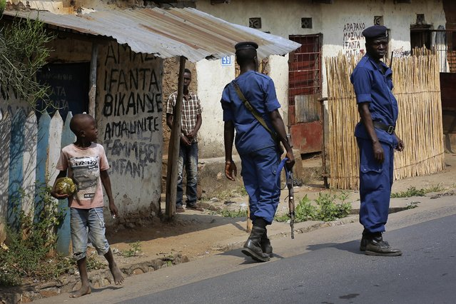 Police keep an eye on the crowds who gathered for the funeral procession of Emmanuel Ndere Yimana, an opposition supporter assassinated Wednesday July 21 2015, in Bujumbura, Burundi, Thursday July 22, 2015. (Photo by Jerome Delay/AP Photo)