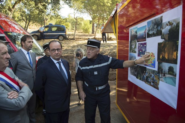 France's President Francois Hollande (C) listens during a visit with fire fighters in Bormes-les-Mimosas, France, July 27, 2015 as part of a one-day trip to the Var region, focusing on efforts to combat forest fires and maritime police action. (Photo by Bertrand Langlois/Reuters)
