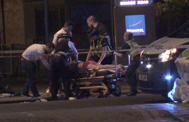 In this image made from PA Video footage, people receive medical attention in Thrale Street near London Bridge following a terrorist incident Sunday, June 4, 2017. Terrorism struck at the heart of London, police said Sunday, after a vehicle veered off the road and mowed down pedestrians on London Bridge and gunshots rang out amid reports of knife attacks at nearby Borough Market. (Photo by Federica De Caria/PA Wire via AP Photo)