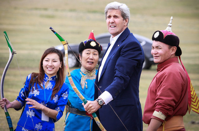 US Secretary of State John Kerry (2R) reacts after shooting a bow and arrow as he participates in a Naadam ceremony, a competition which traditionally includes horse racing, Mongolian wrestling and archery, in Ulan Bator, Mongolia on June 5, 2016. (Photo by Byambasuren Byamba-Ochir/AFP Photo)