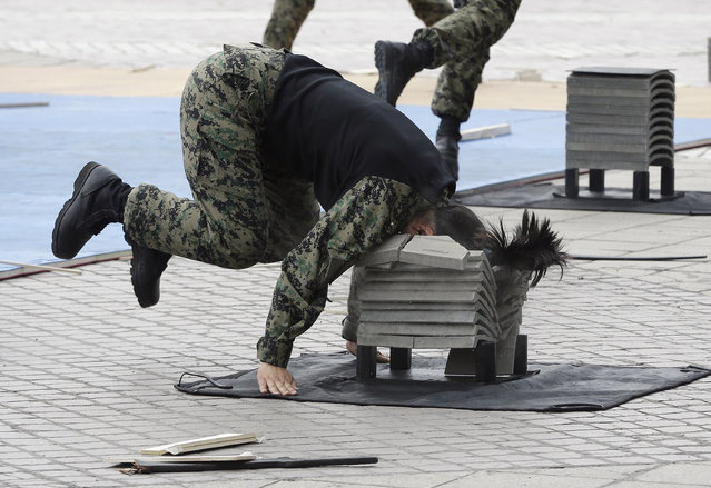 A soldier from the South Korean army special forces breaks stone plates with her head during a martial arts demonstration for Memorial Day at Korea War Memorial Museum in Seoul, South Korea, Monday, June 6, 2016.(Photo by Ahn Young-joon/AP Photo)