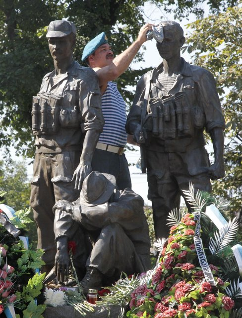 A Ukrainian paratrooper veteran cleans the monument to soldiers killed in Afghanistan in the 1979-1989 war to mark Paratrooper Day in Kiev, Ukraine, Sunday, August 2, 2015. Close to 2,000 Ukrainian soldiers have been killed in Ukraine's east since the beginning of a war conflict with pro-Russian separatists, some 1,000 soldiers  more remained unidentified, according to Ukraine's Defense Ministry. (Photo by Efrem Lukatsky/AP Photo)