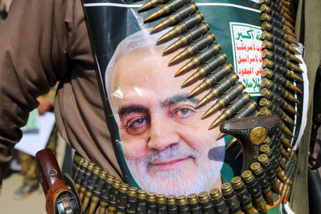 "A supporter of the Houthis has a poster attached to his waist of Iranian Major-General Qassem Soleimani, head of the elite Quds Force, who was killed in an air strike at Baghdad airport, during a rally to denounce the U.S. killing, in Saada, Yemen January 6, 2020. The writing on the poster reads: ""God is the Greatest, Death to America, Death to Israel, Curse on the Jews, Victory to Islam"". (Photo by Naif Rahma/Reuters)"