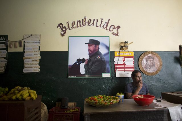 A photograph of Cuba's former President Fidel Castro decorates a wall inside a state's run market as Yorquis Camacho, 39, waits for customers, Havana, July 20, 2015. (Photo by Alexandre Meneghini/Reuters)