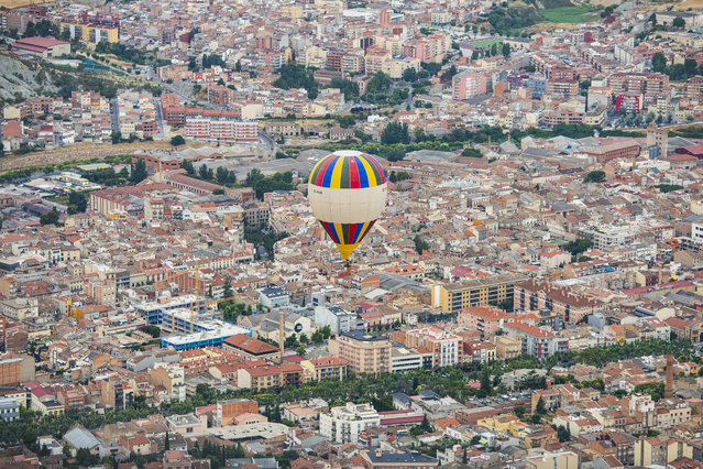 A hot-air balloon flies over Igualada, near Barcelona, during the 21th European Balloon Festival, on July 6, 2017. The European Balloon Festival, is the largest one in the country and one of the biggest in Europe. The first edition was held in 1997 and since then it has been held every year. (Photo by Josep Lago/AFP Photo)